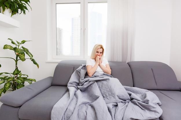 깨어 있는 동안 그녀의 침대에 앉아 아픈 여자