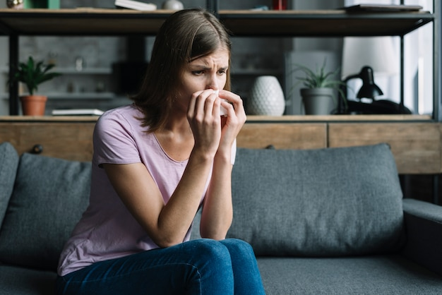 Sick woman sitting on sofa blowing nose with tissue paper