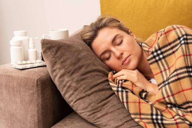 담요 아래에서 잠자는 아픈 여자