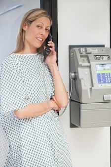 Sick woman smiling and using payphone