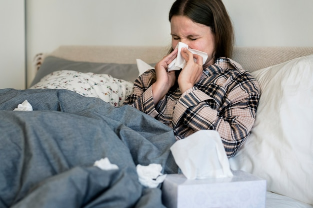 Sick woman sneezing in bed