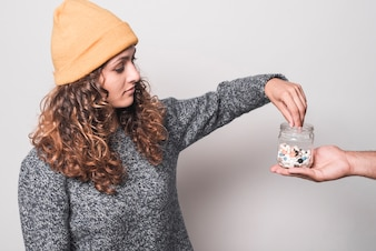 Sick woman taking pills from bottle against white background