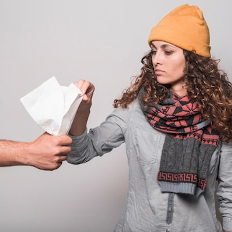 Sick woman taking tissue paper from man's hand against gray background