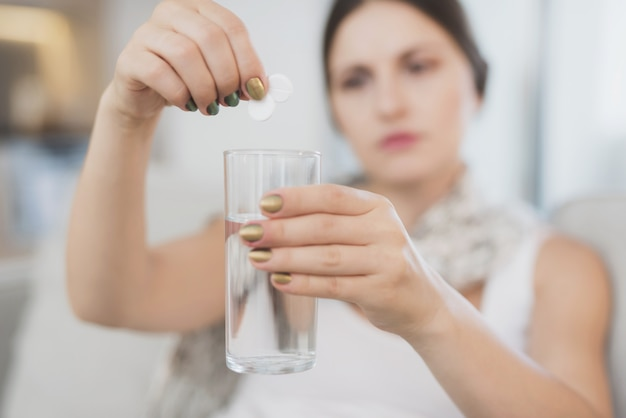 Sick woman throws two tablets into a glass of water.