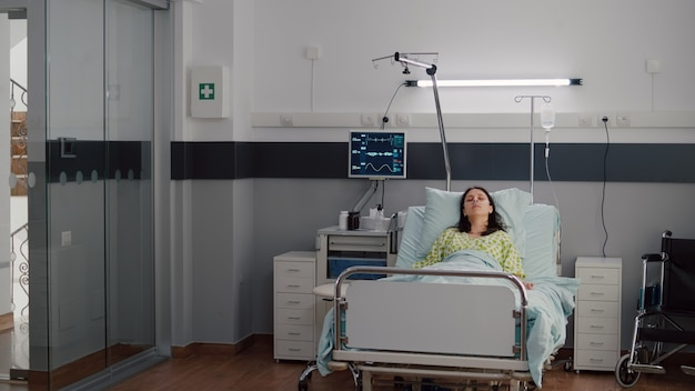 Sick woman wearing nasal oxygen tube resting in bed falling asleep