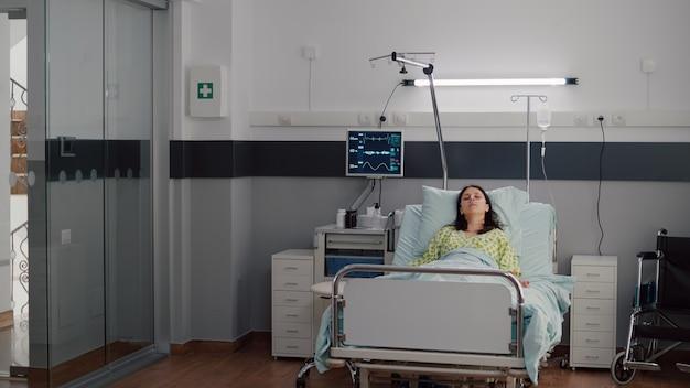 眠りに落ちるベッドで休んでいる鼻酸素チューブを身に着けている病気の女性
