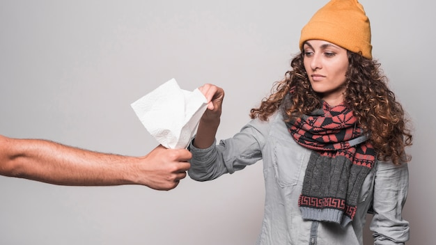 Sick woman wearing scarf around her neck holding tissue paper against gray background
