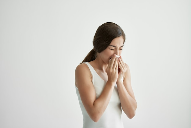 Sick woman in white tank top handkerchief runny nose health problems cold flu