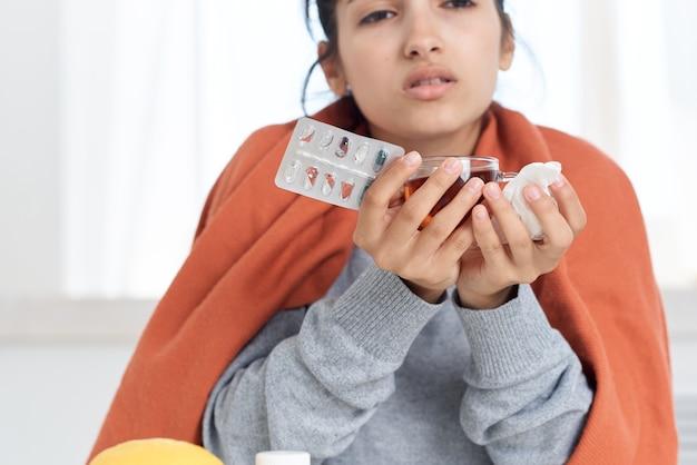 Больная женщина с одеялом на плечах таблетки лекарства холодный чай в руках