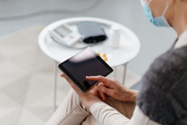 Больная женщина с цифровым планшетом, сидя на диване.