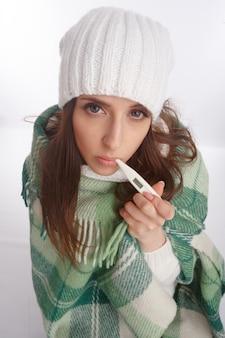 彼女の口の中の温度計にかかった女性