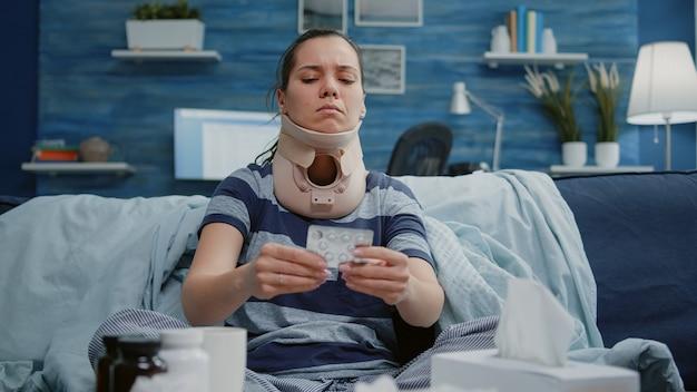 Donna malata con la schiuma del collo cervicale che legge l'etichetta delle pillole di farmaci