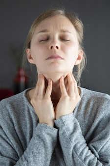 Sick woman with closed eyes having sore throat, touching neck