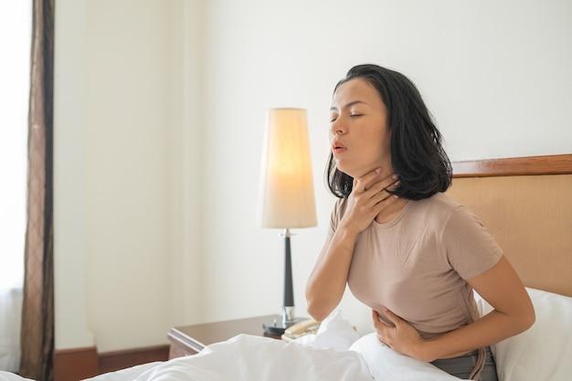 기침하는 동안 얼굴을 덮는 침대에 기침 및 인후 감염으로 아픈 여자