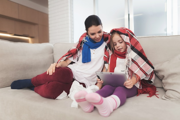Sick woman with daughter are watching a tablet.