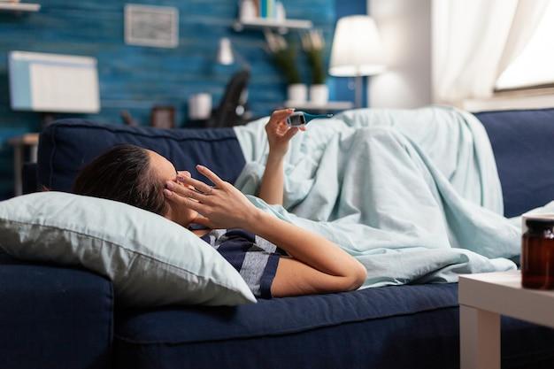 발열 감기와 독감 집에서 온도계로 온도를 측정하는 아픈 여자.