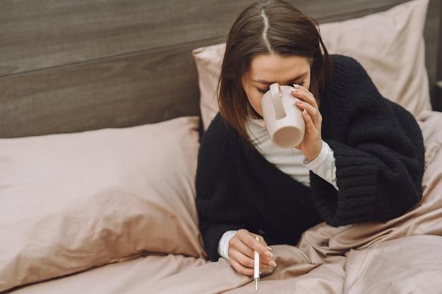 Больная женщина с головной болью сидит дома