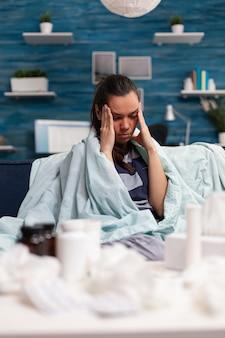 自宅のソファに座って、薬を服用し、風邪のインフルエンザの痛みの熱の治療を受けている頭痛のある病気の女性。片頭痛とウイルス症状に苦しんでいる病気や健康上の問題を抱えている人