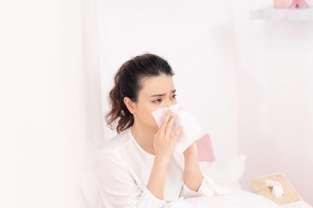Больная женщина с головной болью сидит под одеялом. больная женщина с сезонными инфекциями, гриппом, аллергией, лежа в постели