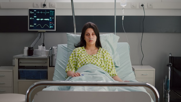 Sick woman with nasal oxygen tube looking into camera resting in bed