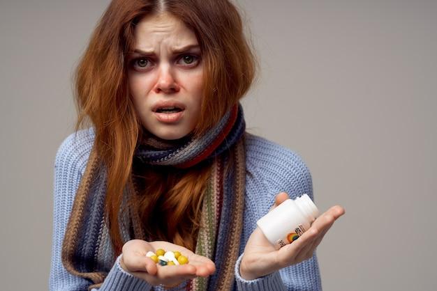 그녀의 손에 비타민 회색 공간 따뜻한 옷 스카프에 약을 가진 아픈 여자
