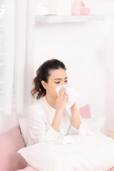 Больная женщина с сезонными инфекциями, гриппом, аллергией, лежа в постели.