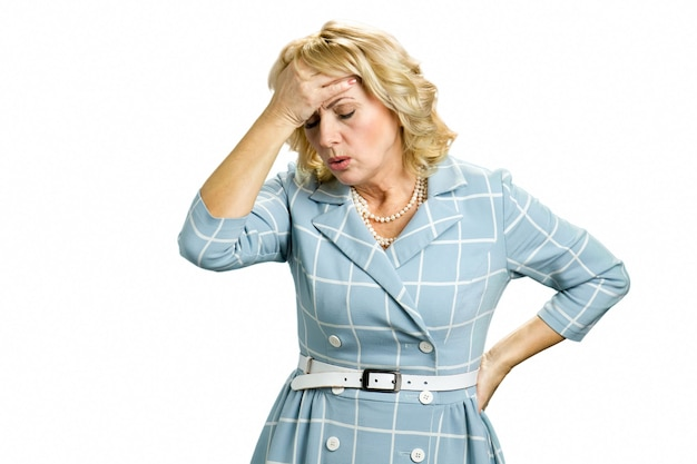 Sick woman with stong headache. mature woman having headache touching her forehead on white close up.