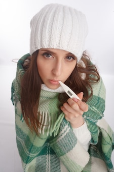 Sick woman with a thermometer in her mouth