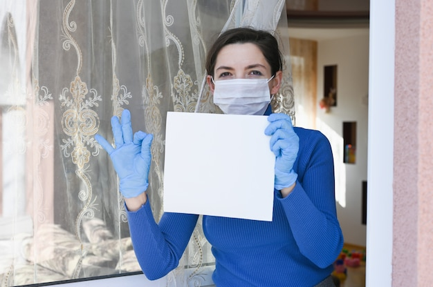 Sick woman with virus protection face mask and gloves looks out of the window