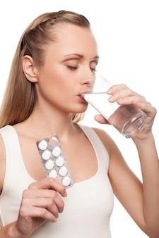 Больная женщина. молодая женщина принимает таблетки и держит глаза закрытыми, стоя изолированной на белом