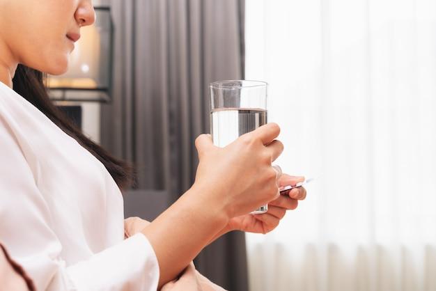 病気の女性の手を握る水、ヘルスケアおよび薬の回復の概念のガラス