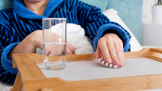 침대 옆 테이블에서 약을 복용하는 아픈 yougn 여자.