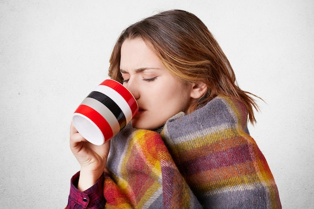 Sick young adorable woman drinks hot tea with honey, wrapped in coverlet, feels cold in winter as has high temperatur