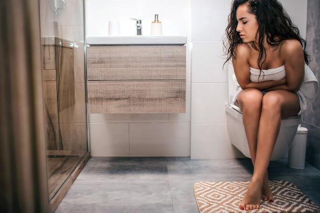 病気の若い黒髪の女性がトイレのトイレに座っています。彼女は胃の問題を抱えています。一人で。痛みと痛み。