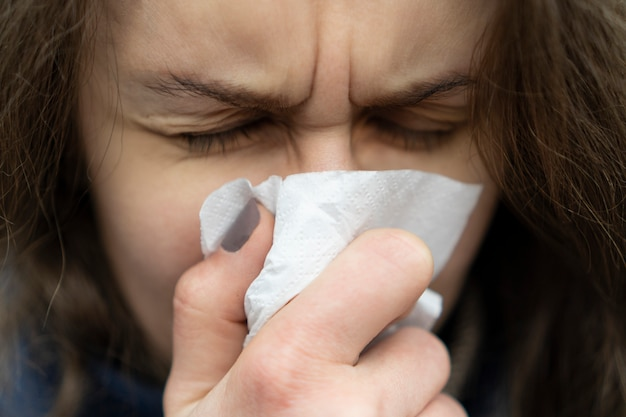 Sick young caucasian woman blowing her nose in a handkerchief standing on the street on cold weather