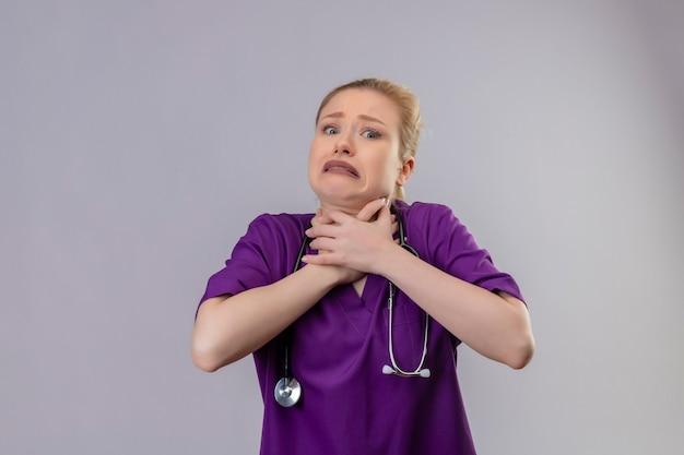 紫色の医療用ガウンと聴診器を身に着けている病気の若い医者は、孤立した白い壁に痛む喉をつかんだ