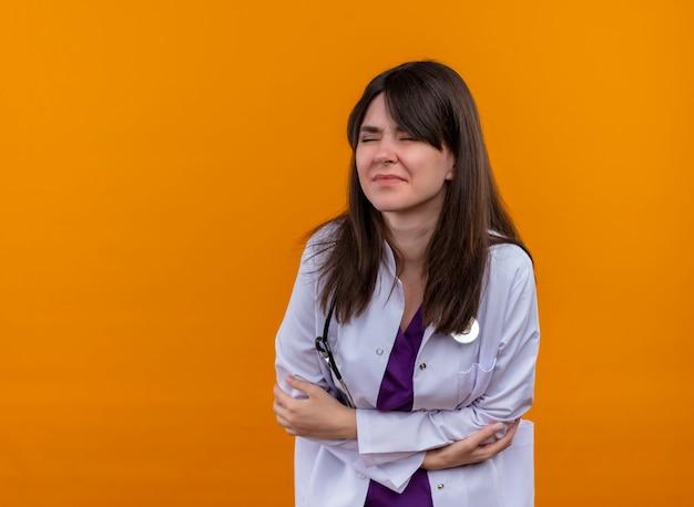 聴診器と医療ローブの病気の若い女性医師は、コピースペースと孤立したオレンジ色の背景に手で腹を保持します。