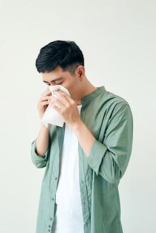 病気の若い男ハンサムでくしゃみは白い壁の壁に隔離されます。病気の概念。アジアの人々。
