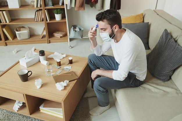 정제, 환약 및 손수건으로 테이블 앞에 소파에 앉아있는 동안 그의 체온을 측정하는 의료 마스크에 아픈 젊은 남자