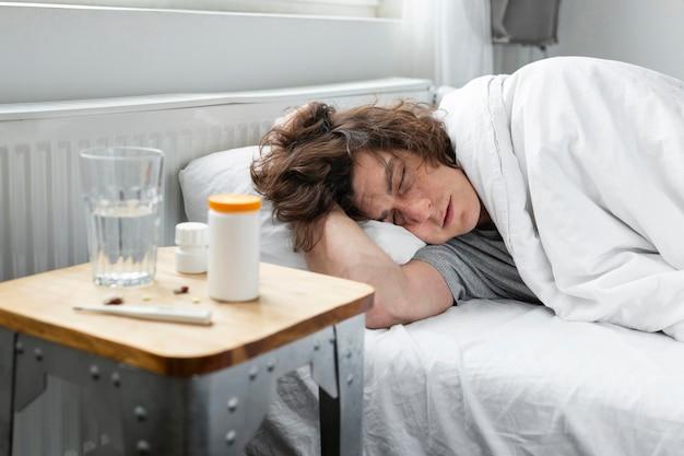 Больной молодой человек отдыхает в постели