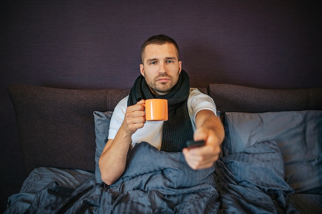 Sick young man sits on bed in bedroom and uses remote control. he looks straight forward. guy has orange cup in hands. he is calm and concentrated. there are scarf arounf his neck.