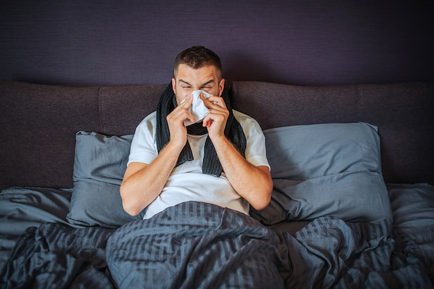Sick young man sits on bed. he is covered with blanket. guy sneezing into tissue. he suffers. young man feels terrible. he is concentrated on sneezing.