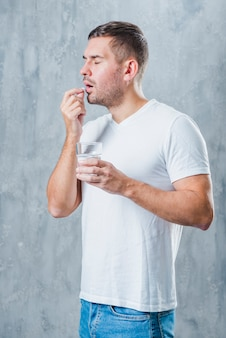 Sick young man standing against gray backdrop holding water glass in hand taking pill