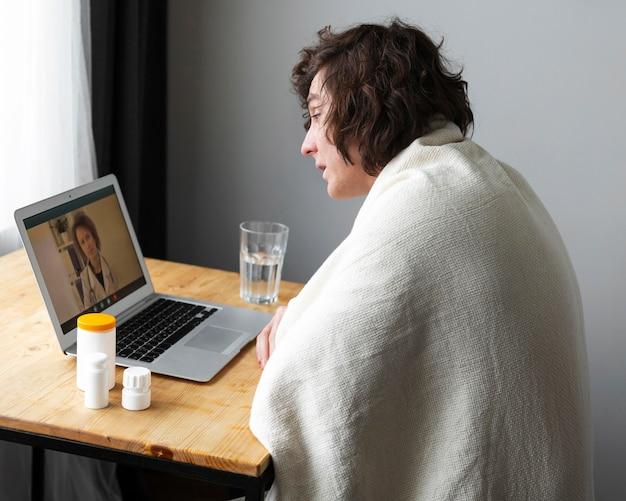그의 의사에게 온라인으로 이야기하는 아픈 젊은 남자
