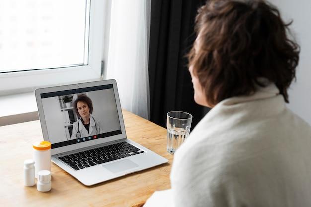 Больной молодой человек разговаривает со своим врачом онлайн