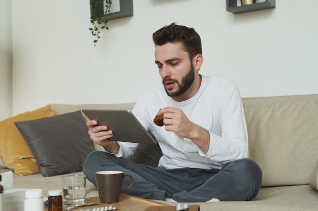 독감 또는 코로나 바이러스가있는 아픈 청년이 약 병을 들고 질병 중에 집에 머무르는 동안 온라인 의사와 상담
