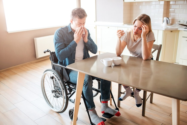 テーブルで健康な女性とくしゃみをする包括性を持つ病気の若い男