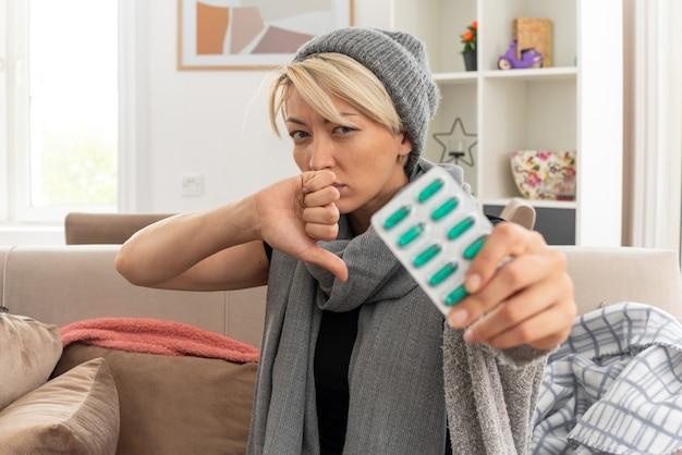 Malati giovane donna slava con sciarpa intorno al collo indossando cappello invernale tenendo la medicina blister e pollice verso il basso seduto sul divano in soggiorno