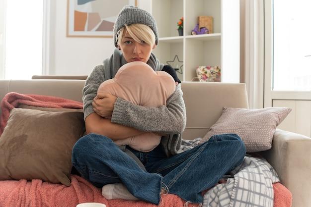 거실에서 소파에 앉아 베개를 껴안고 겨울 모자를 쓰고 목에 스카프를 두른 아픈 젊은 슬라브 여성