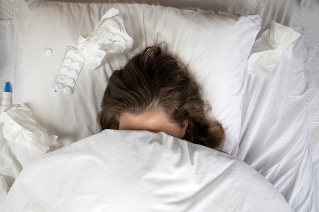 A sick young woman in bed, lying with her head under the blankets and a pile of tissues next to her